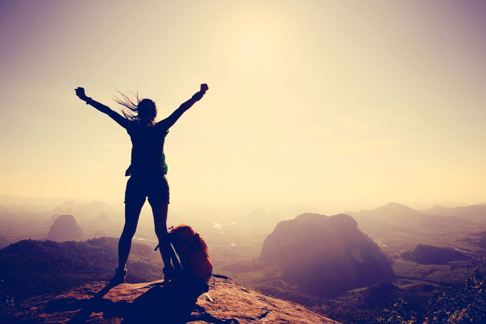 54974893 - silhouette of cheering woman hiker open arms at mountain peak