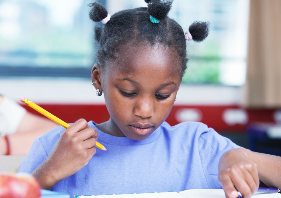 35508656 - afro american female student doing school work in classroom.
