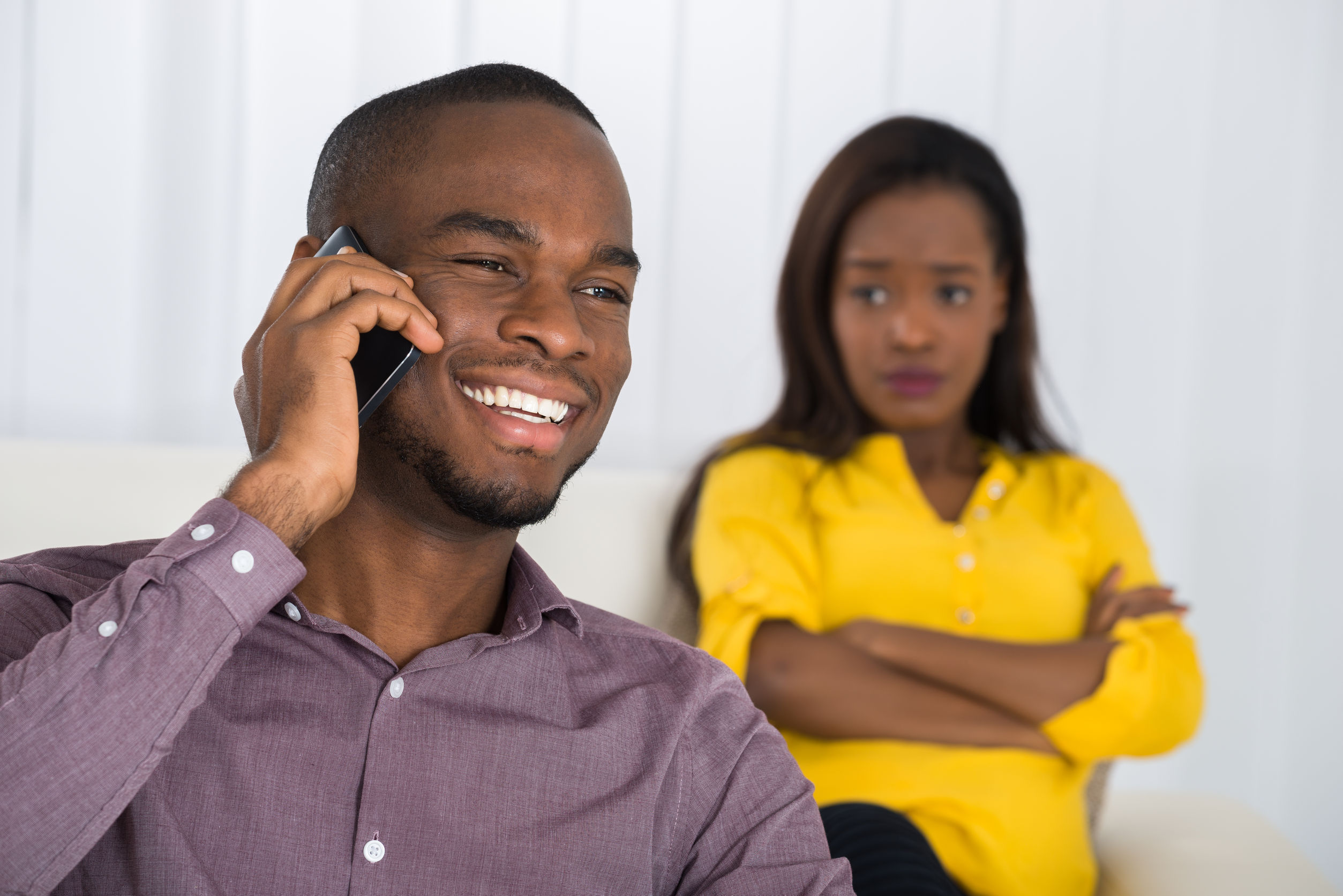 56064696 - young woman looking at man talking on cellphone at home
